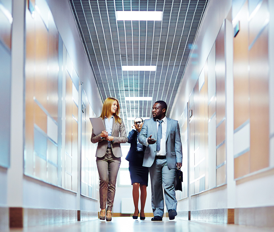 group of people two women and a man walking in an office