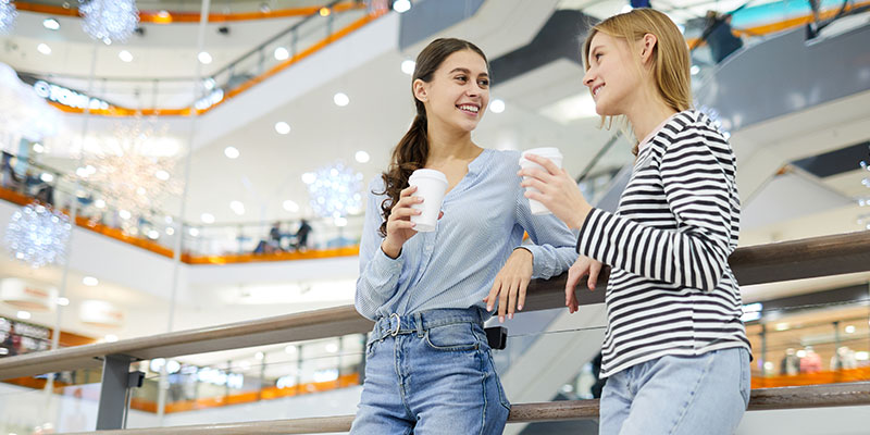 two girls drinking a coffee in a shopping centre
