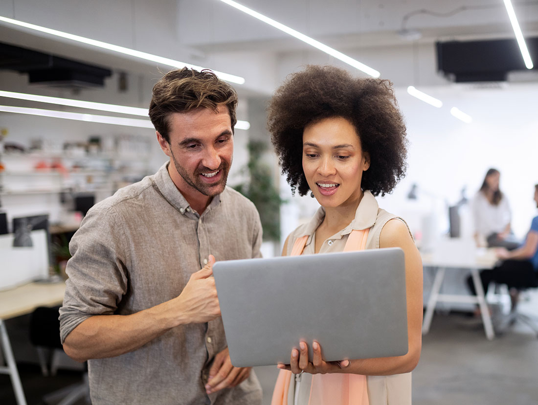 a woman showing something on a laptop to a man in an office