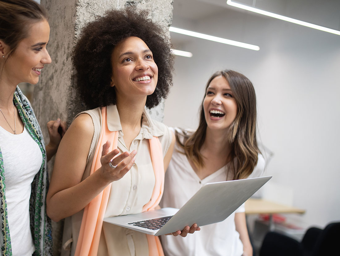 a woman holding a laptop and smiling with two other women